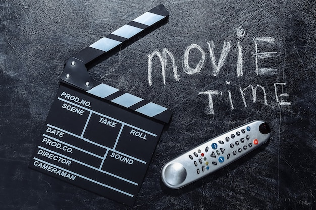 Filmzeit. filmklappe und tv-fernbedienung auf kreidetafel.
