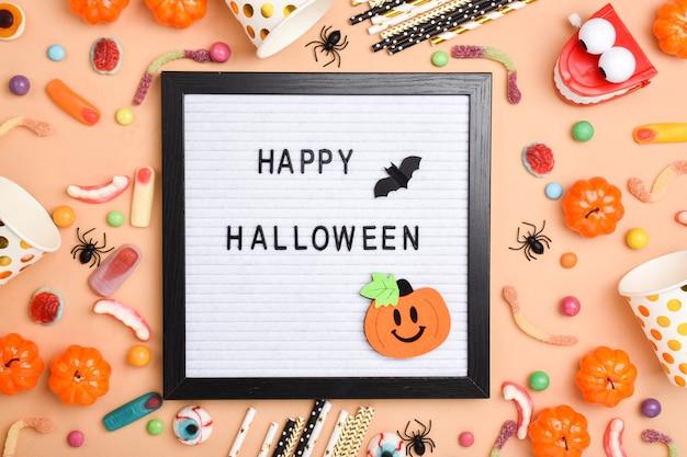 Filzbrett mit happy halloween-text und verschiedenen süßigkeiten auf orangefarbenem hintergrund mit platz für text. flaches layout, draufsicht, ein ort zum kopieren.