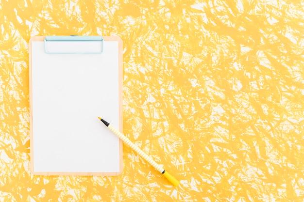 Filzstift auf klemmbrett über dem gelben strukturierten hintergrund