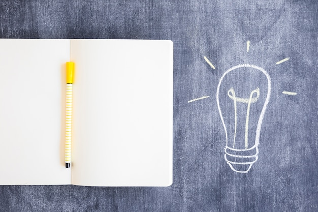 Filzstift auf leerem notizbuch mit gezogener glühlampe auf tafel