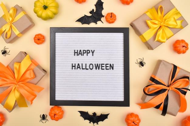 Filztafel mit der aufschrift happy halloween auf dem hintergrund von geschenken, kürbissen und spinnen auf beigem hintergrund. ansicht von oben.