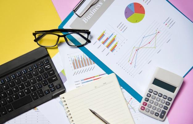 Finanz- und geschäftsdiagrammdiagrammreportpapierdokument mit offenem notizbuchpapier des taschenrechners