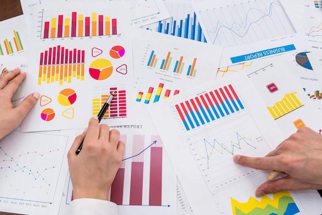 Finanzanalysten, die mit geschäftsgrafiken und diagrammen arbeiten