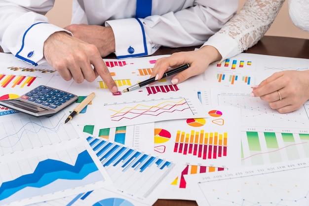 Finanzanalysten, die mit geschäftsgraphen und -diagrammen arbeiten