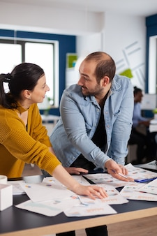 Finanzberater diskutiert mit geschäftsfrau des start-ups über statistikdiagramme, die sich gegenseitig ansehen