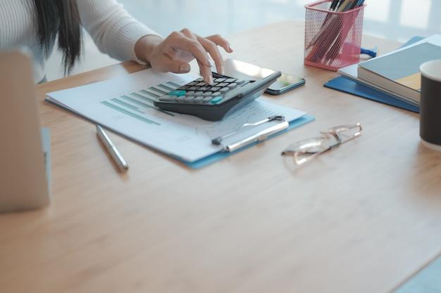Finanzberater verwenden taschenrechner, um einnahmen und budget zu berechnen. buchhalter, der buchhaltung macht. buchhalter macht berechnung