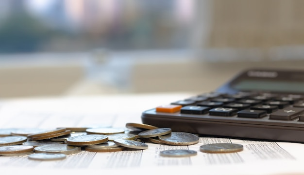 Finanzbericht mit münzen und taschenrechner auf schreibtischtabelle.