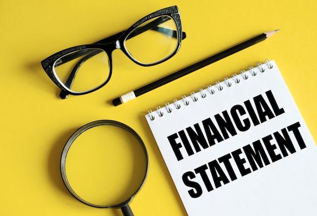 Finanzberichtstext geschrieben auf einem notizbuch mit stiften, brille und lupe