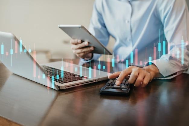 Finanzbuchhaltungskonzept. geschäftsmann, der mit tablet arbeitet und einen taschenrechner verwendet, um die anzahl der statik im büro zu berechnen.