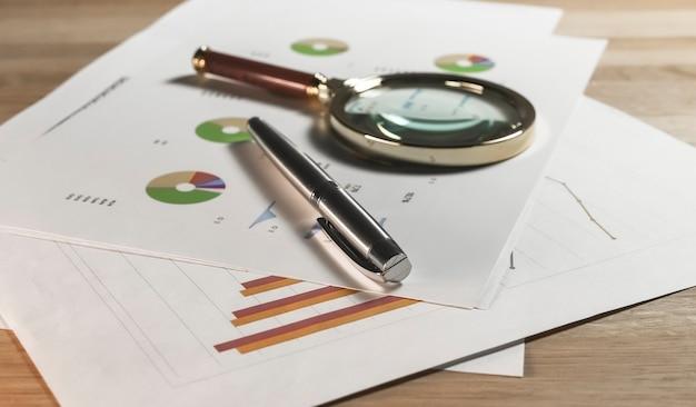 Finanzdiagramm auf papieren mit lupe und stiftgeschäftsbuchhaltungsdokumenten mit diagramm und...