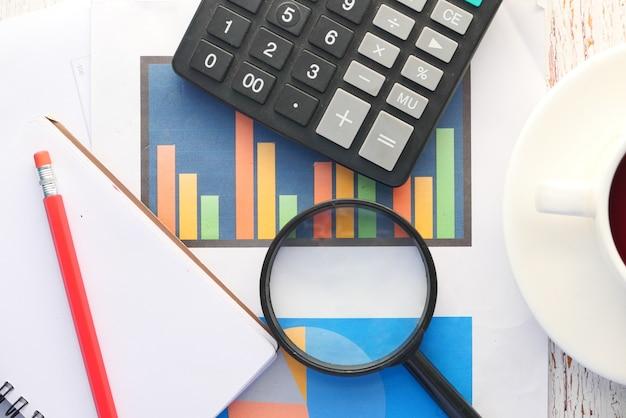Finanzdiagramm, lupe und notizblock auf dem tisch