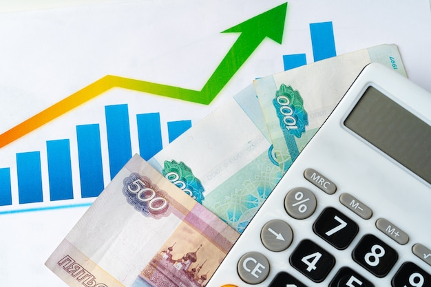 Finanzdiagramm mit geldstapel der russischen rubel mit taschenrechner. währungsaufwertungskonzept