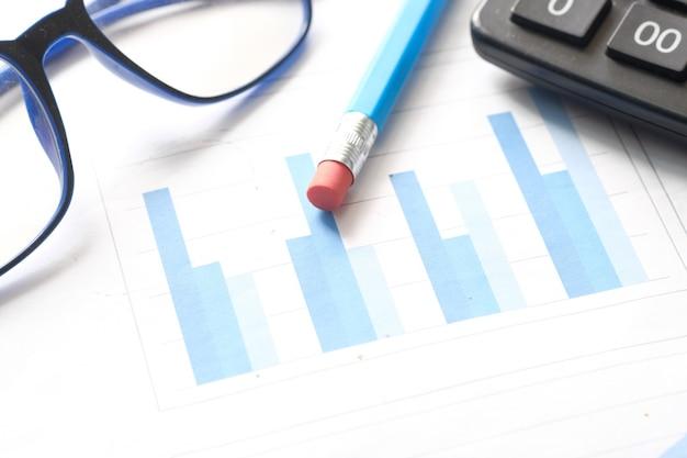 Finanzdiagramm, taschenrechner und notizblock auf dem tisch.