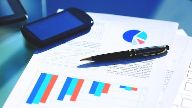 Finanzdiagramme auf dem tisch mit tablette und stift