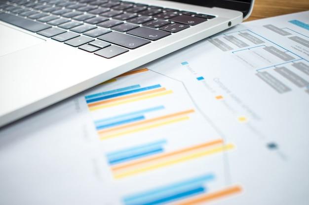 Finanzdiagramme und computer stehen auf dem holztisch im geschäftskonzept.