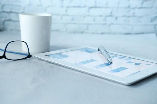 Finanzdiagramme werden auf einem digitalen tablet auf einem bürotisch angezeigt.