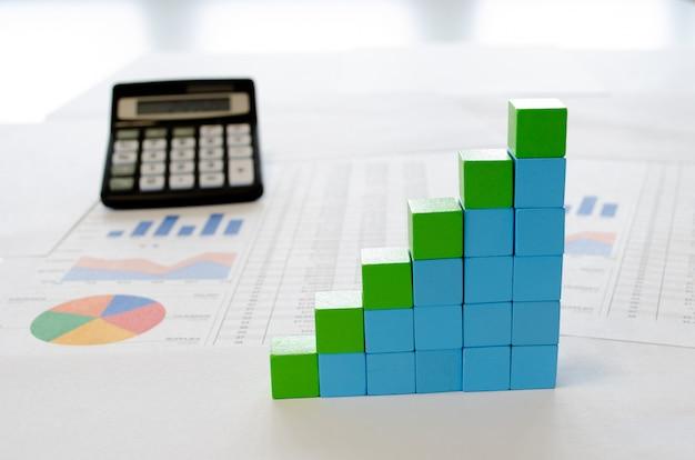 Finanzdokumente mit blauen und grünen würfeln, die in einem säulendiagramm als konzept für wachstum, ertrag oder umsatz angeordnet sind