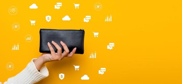 Finanzen asiatische frau mit einer schwarzen brieftasche voller geld bereit zum einkaufen die finanzen sind gestrafft, erfolgreich im finanz- und bankwesen. auf gelbem grund