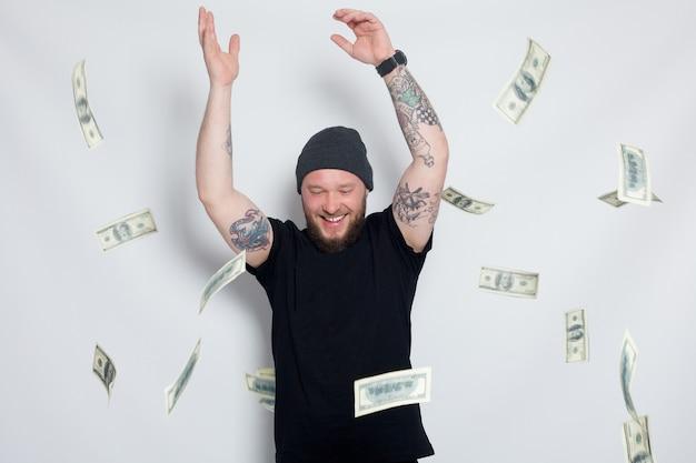 Finanzen, leute, lifestyle-konzept - junger mann mit geld zur kamera. dollar. mode porträt junger bärtiger mann. lächelnder hut des hippie-boy.handsome mann. brutaler bärtiger junge mit tattoo