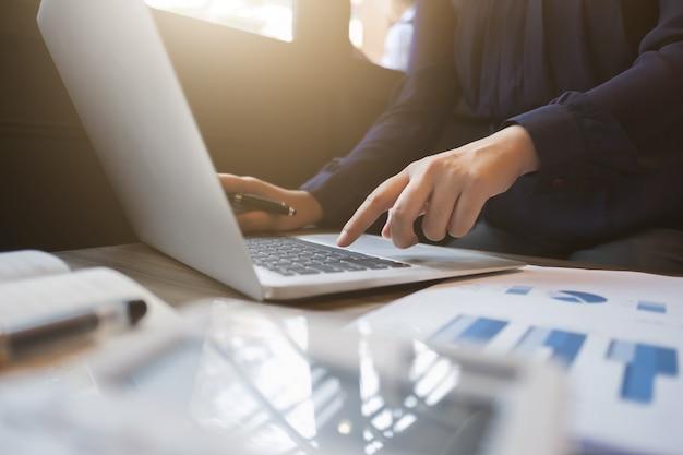 Finanzexekutive, die an investitionsdaten mit dokumenten und laptop arbeitet
