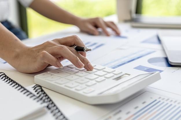 Finanzgeschäftsfrau, die einen weißen taschenrechner drückt, verwendet sie einen taschenrechner, um die zahlen in den finanzdokumenten des unternehmens zu berechnen, die mitarbeiter in der abteilung als besprechungsdokumente erstellen.