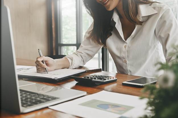 Finanzhauptplanung, frau, die an notizbuchpapier mit bürofinanzversorgungen auf schreibtisch arbeitet.