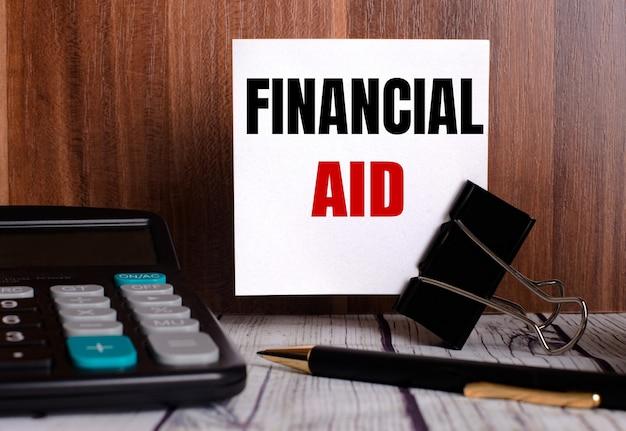 Finanzhilfe steht auf einer weißen karte an einer holzwand neben einem taschenrechner und einem stift.