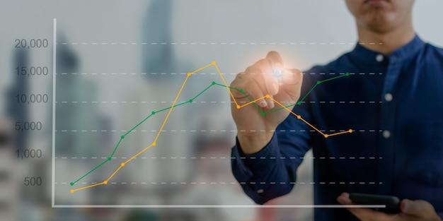 Finanzielle grafiken und diagramme wirtschaftliche geschäftskonzepte, investitionen. hand, die einen stift hält, der die virtuelle bildschirmschnittstelle des digitalen geschäftsdiagramms berührt.