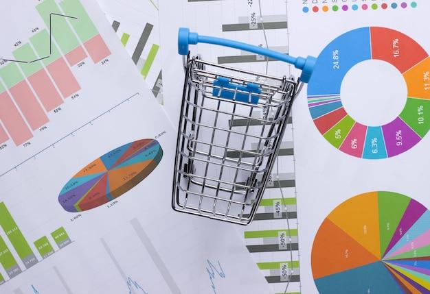 Finanzielle verkaufsstatistik. einkaufswagen mit grafiken und diagrammen. wirtschaft und finanzen, analytik