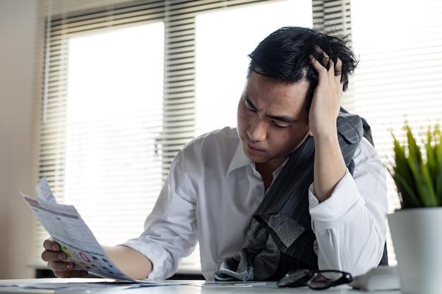 Finanzielles problemkonzept. der junge asiatische mann ist gestresst und überlegt durch schulden von vielen kreditkarten und rechnungen. der mensch hat einen weg aus der verschuldung gefunden.