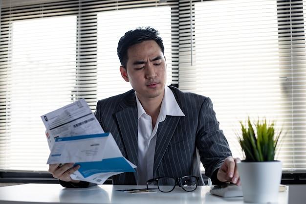 Finanzielles problemkonzept. man berechnet die schulden mit einem taschenrechner. der junge asiatische mann ist gestresst und überlegt durch schulden von vielen kreditkarten und rechnungen.