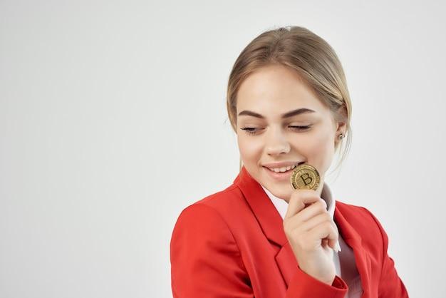 Finanzier in einer roten jacke goldmünze bitcoin isolierten hintergrund. foto in hoher qualität