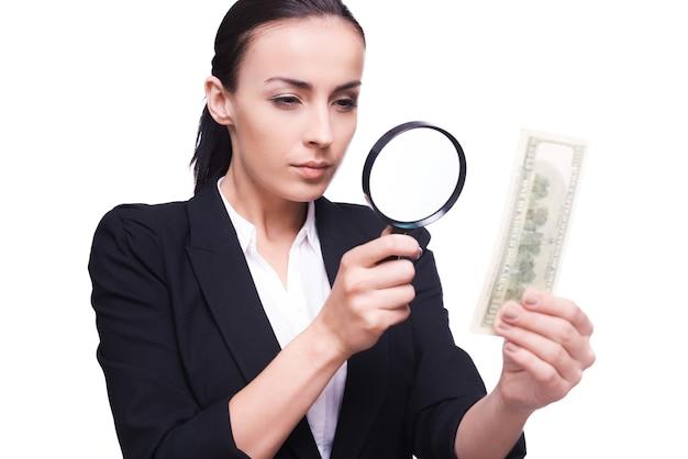 Finanzinspektor. selbstbewusste geschäftsfrau, die durch eine lupe auf einen hundert-dollar-schein schaut