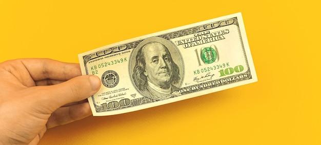 Finanzinvestitionskonzept, mannhand hält eine banknote, einen hundert-dollar-schein auf einem gelben hintergrund des geschäftsdesktops