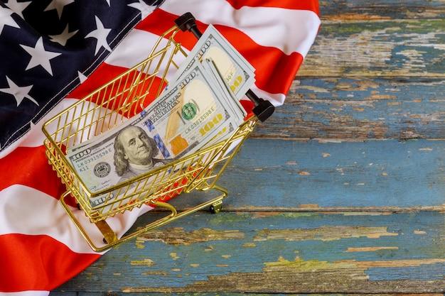 Finanzkonzept des einkaufswagens mit us-dollar-banknoten auf amerikanischer flagge