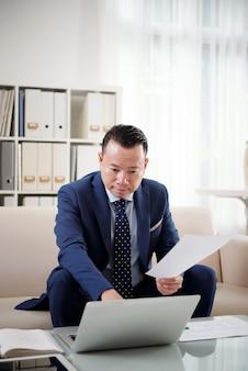 Finanzmanager, der bericht über seinen laptop unter bezugnahme auf ausdruckdokumentation vorbereitet