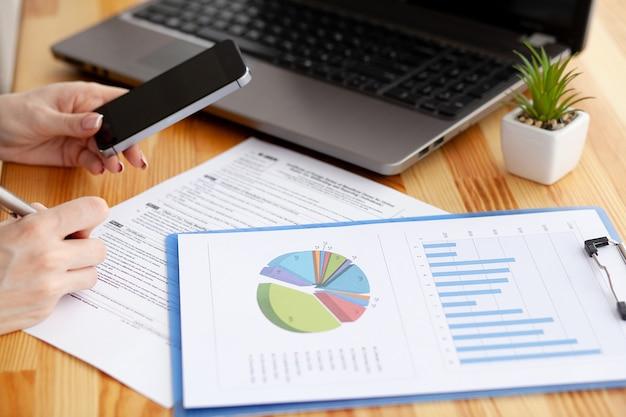 Finanzmanager, der im schreibtisch sitzt und mit finanzdokumenten firma arbeitet
