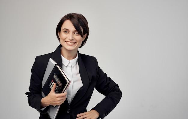 Finanzmodellfrau in schwarzer jacke mit dokumenten in den händen.