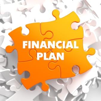 Finanzplan auf orange puzzle auf weißem hintergrund.