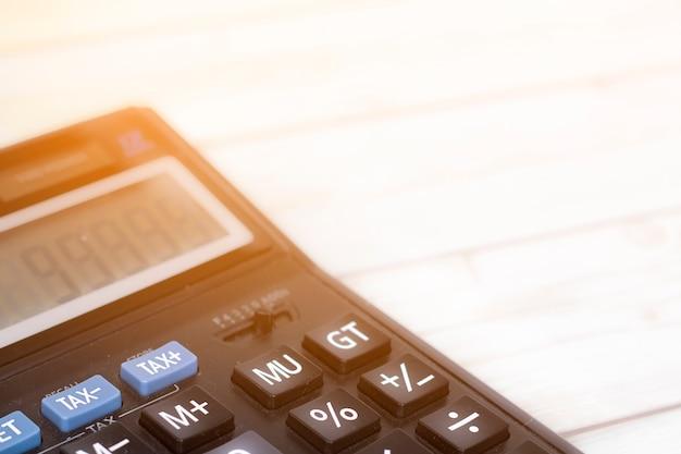 Finanzsteuer und gewinn auf taschenrechner im innenministerium auf hölzernem schreibtisch, abschluss herauf knopf