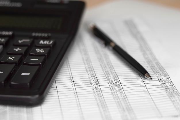 Finanzwirtschaftliche berechnung und stift auf braunem hintergrund