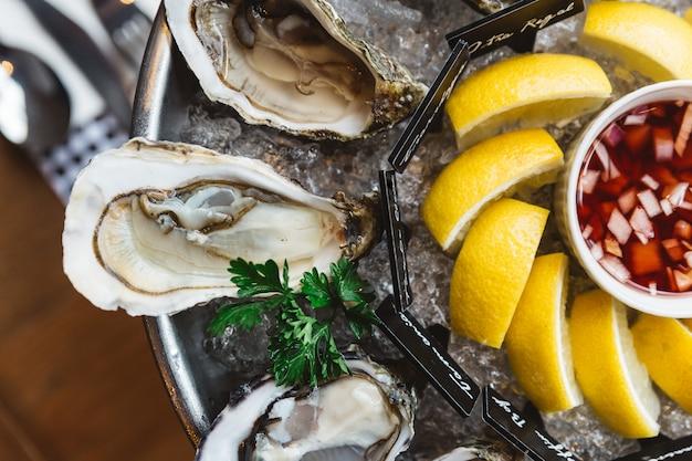 Fine de claire oyster und viele arten von frischen austern, serviert in rundem tablett mit zitronenscheibe und würziger sauce.