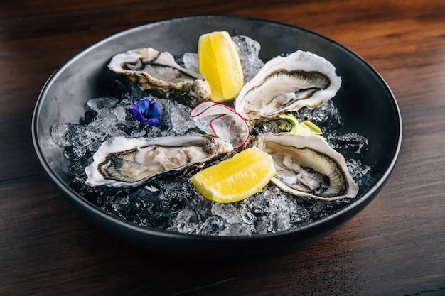 Fine de claire oyster und zitrone serviert in schwarzer schale mit eis auf holztisch.