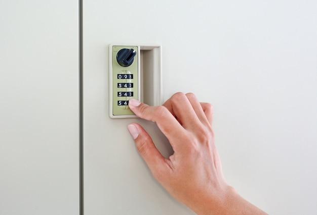 Finger am kombinationscodeschloss an der schranktür des safes
