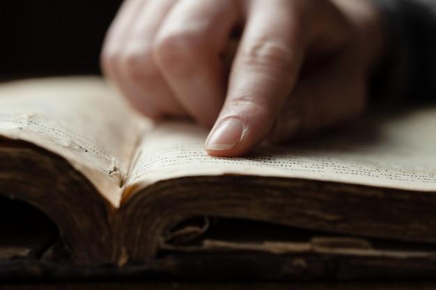 Finger auf ein altes buch oder eine bibel