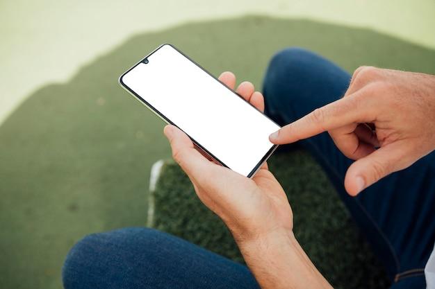 Finger, der auf telefon des leeren bildschirms zeigt