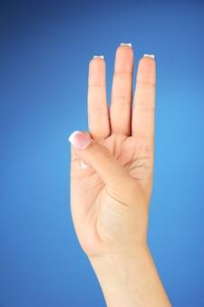 Finger, der das alphabet in der amerikanischen gebärdensprache (asl) buchstabiert. buchstabe w