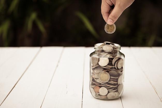Finger, der die münze füllt in die glasflasche mit münzen des vollen niveaus in der flasche hält
