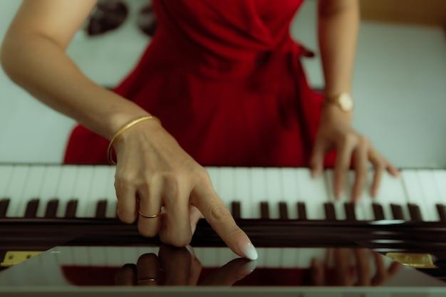 Finger der frau, die auf dem tablet-computerbildschirm für grundlegende klaviervideolektionen berührt, während sie online lernt, wie man spielt. konzept der neuen fähigkeit für quarantäne-personen zu hause während des ausbruchs des coronavirus.