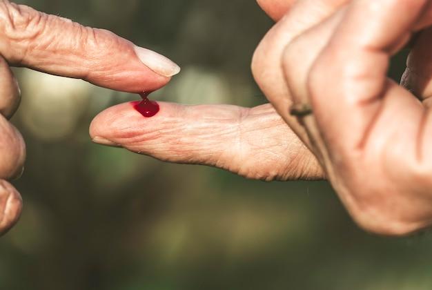 Finger des mannes und der älteren frau mit blut